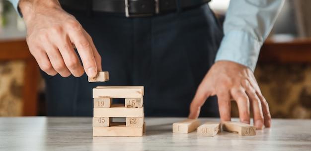 Zakenman spelen met houten blokjes op het bureau