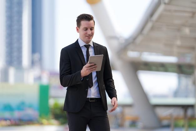 Zakenman staan met het gebruik van een digitale tablet in staande voor moderne kantoorgebouwen
