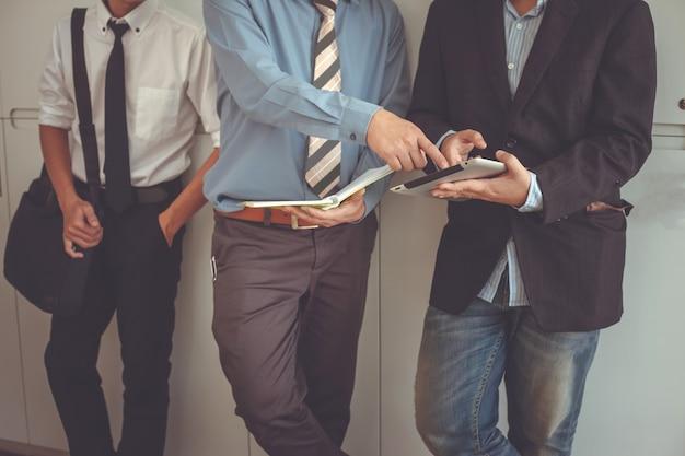 Zakenman, staand, klesten mensen uit het bedrijfsleven met behulp van een digitale tablet.