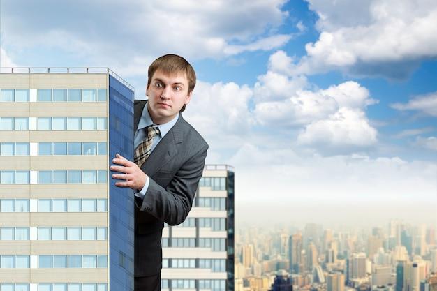 Zakenman staat achter de wolkenkrabbers tegen de blauwe lucht