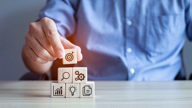 Zakenman stapel bos blok stap op tafel met pictogram bedrijfsstrategie en actieplan