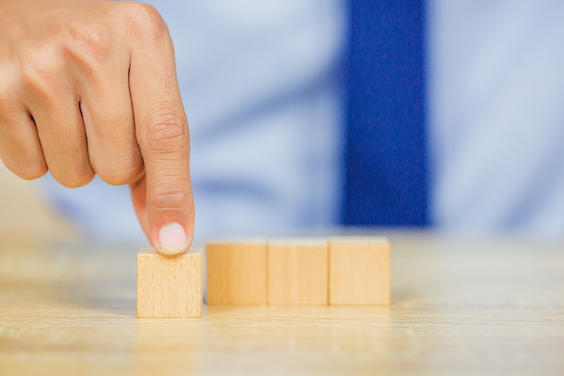 Zakenman stapelen houten blokken in stappen. concept van bedrijfsgroei succes