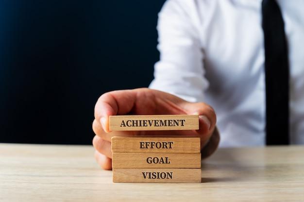 Zakenman stapelen houten pinnen met elementaire woorden voor zakelijk succes - visie, doel, inspanning en prestatie. over blauwe achtergrond.