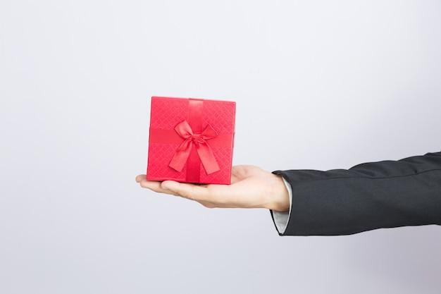 Zakenman steekt de rode geschenkdoos
