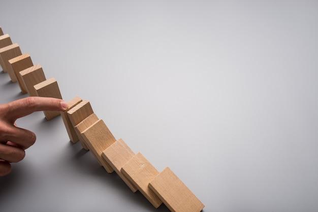 Zakenman stoppen domino-effect met zijn vinger op grijze achtergrond met kopie ruimte.