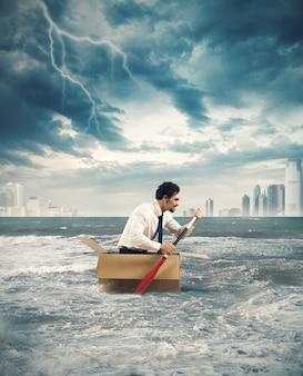 Zakenman surft op een karton tijdens storm