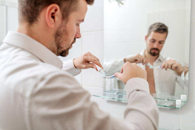 Zakenman tandpasta op de borstel zetten terwijl hij voor spiegel in de badkamer staat.