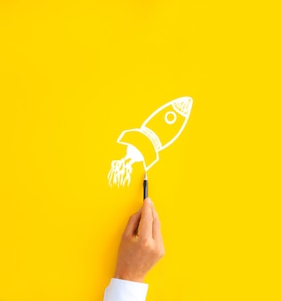 Zakenman tekening startende raket. bedrijfsconcept opstarten, groei en succes.