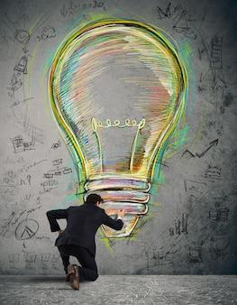 Zakenman tekent op de muur een grote gekleurde lamp met felle kleuren en zakelijke schetsen