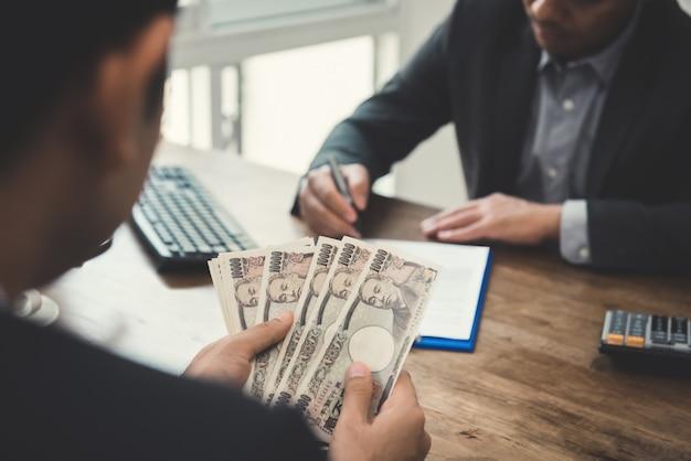 Zakenman tellend geld, japanse yenbankbiljetten, terwijl het maken van een overeenkomst