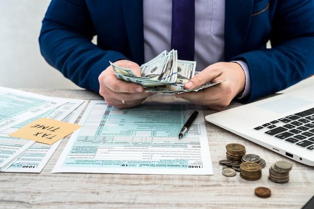 Zakenman telt dollars en vult een individueel belastingformulier van us 1040 in. sticker met inscriptie belastingtijd. fiscaal concept.