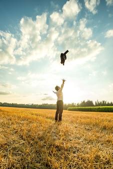 Zakenman throwing coat in de lucht op het veld