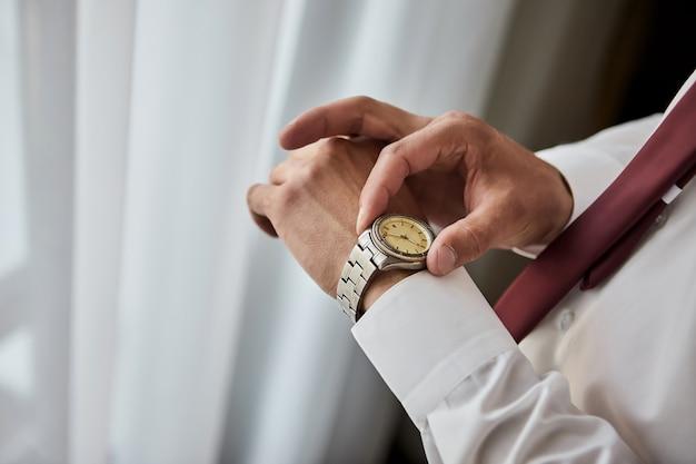 Zakenman tijd op zijn polshorloge controleren, man klok bij de hand zetten, bruidegom klaar in de ochtend voor de huwelijksceremonie. mannenmode