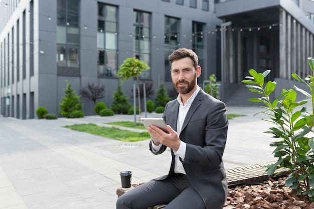 Zakenman tijdens de lunch in de buurt van het kantoor gebruikt een tablet, glimlacht en kijkt naar de camera