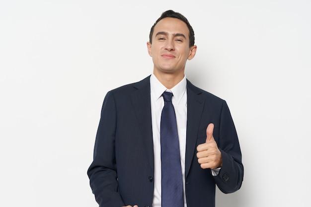 Zakenman toont een positief handgebaar en glimlacht in een klassiek pak