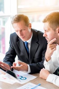 Zakenman twee die businessplan op digitale tablet bespreken