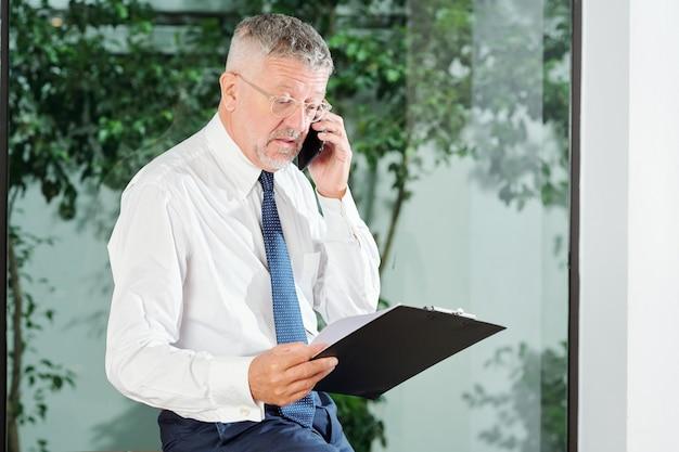 Zakenman van middelbare leeftijd die in glazen document op klembord leest wanneer hij aan de telefoon spreekt met een collega