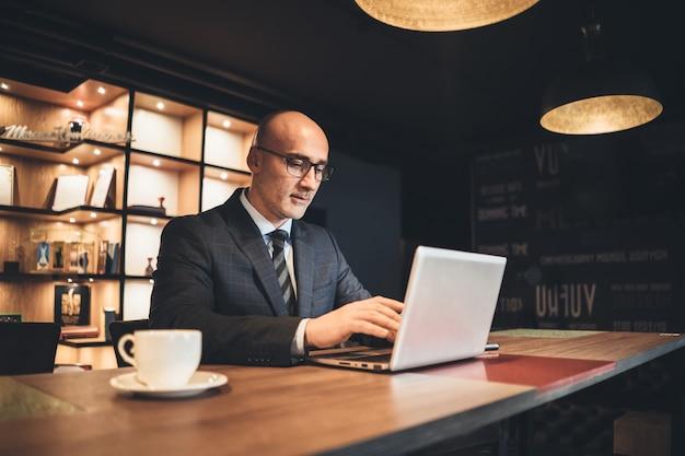 Zakenman van middelbare leeftijd in bedrijfssuite en oogglazen die met behulp van laptop werken