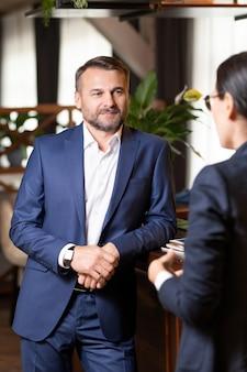 Zakenman van middelbare leeftijd in formalwear staande door toog tijdens interactie met collega