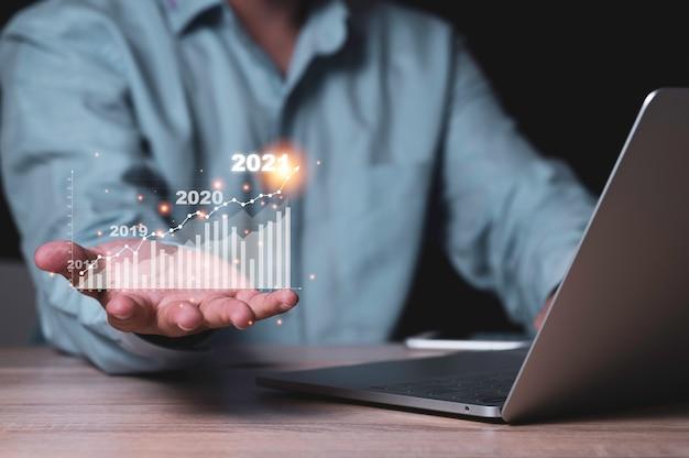 Zakenman vasthouden aan virtuele investeringsbalk en lijngrafiek op houten tafel met laptop als bedrijfsstrategie en aandelenwaarde investeerder concept.