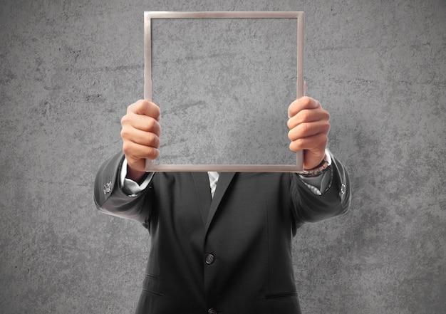 Zakenman verbergt zijn gezicht met een frame