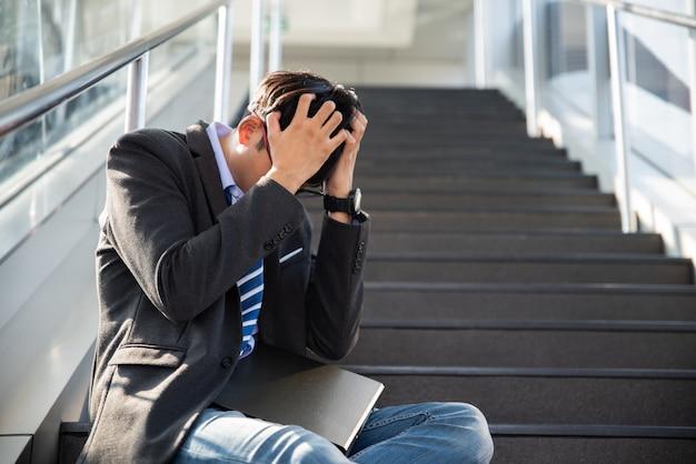 Zakenman verloren in depressie huilen zittend op trappen. benadrukt werkloos concept.