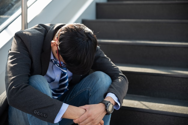 Zakenman verloren in depressie huilende zittend op de trappen van de grondstraat
