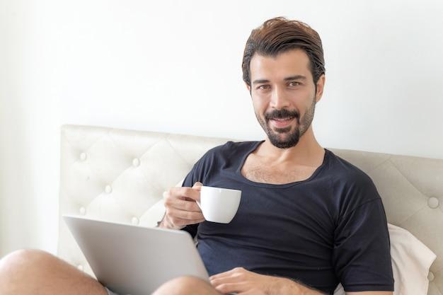 Zakenman voelt zich gelukkig koffie te drinken tijdens het werk op kantoor aan huis