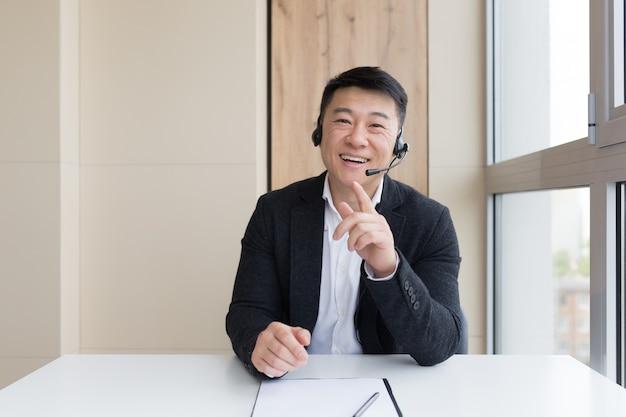 Zakenman voert een online consult uit met zijn handen en legt uit met een headset a