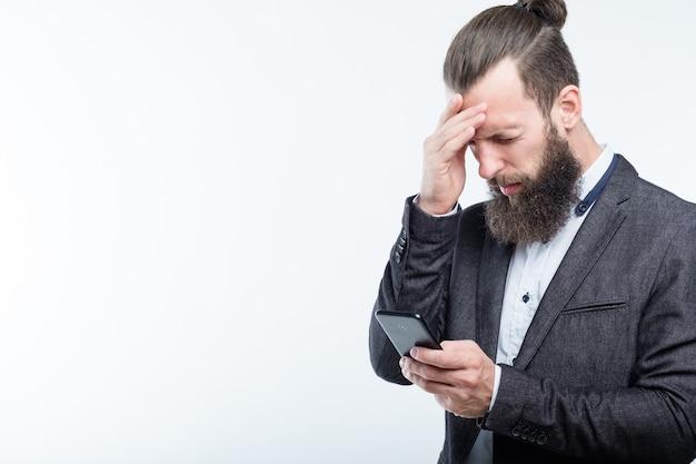 Zakenman voorhoofd aan te raken en telefoon vast te houden. hoofdpijn vermoeidheid en overbelasting.