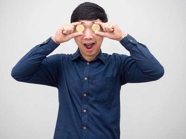 Zakenman vrolijk dicht bitcoin op zijn gezicht verbaasd op een witte achtergrond