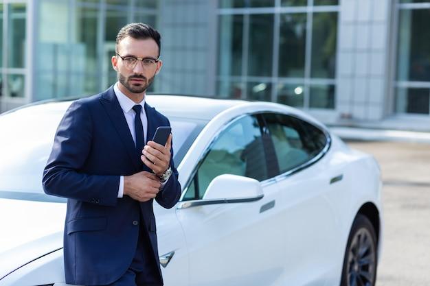 Zakenman wachten. donkerharige zakenman die in de buurt van een witte auto staat terwijl hij op zijn vrouw wacht