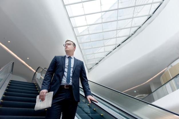 Zakenman walking down escalator concept