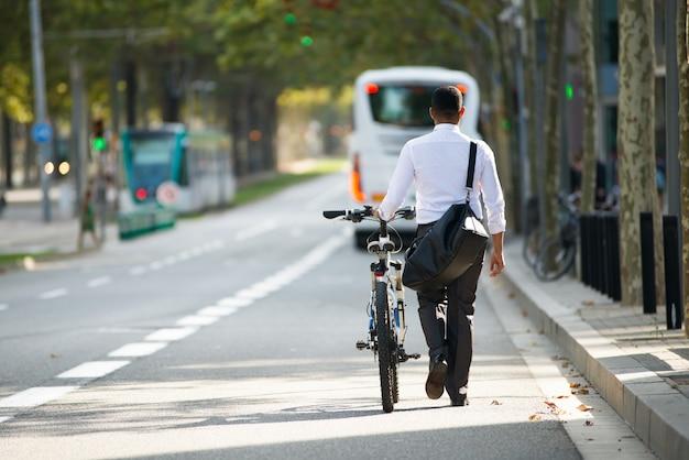 Zakenman wandelen met fiets in straat na werk