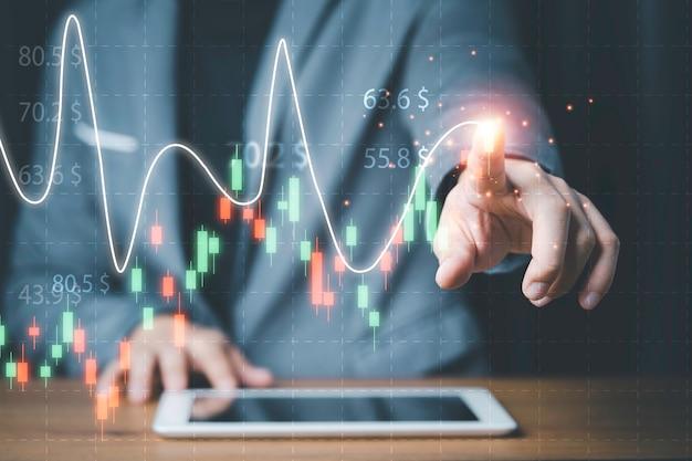 Zakenman wat betreft de technische grafiek van de beurs op het virtuele scherm van de tablet voor analyse van financiële informatiegegevens