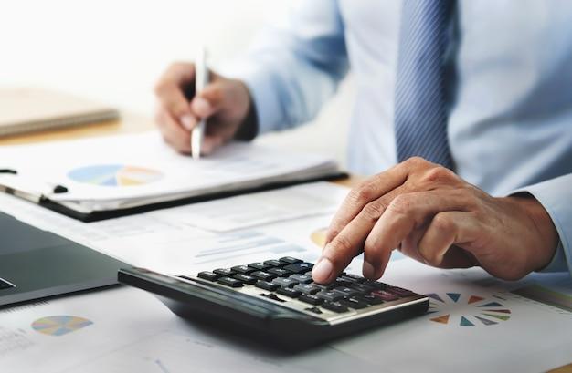 Zakenman werken met calculator in kantoor. financiën en boekhoudkundig concept