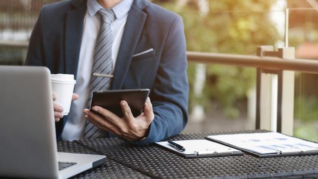 Zakenman werken met digitale tablet en laptop met financiële bedrijfsstrategie in een cafe koffie