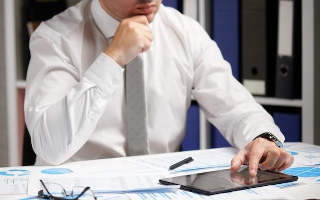 Zakenman werken met tablet-pc, berekenen, lezen en schrijven van rapporten. beambte, tafel close-up. bedrijfsconcept financiële boekhouding.