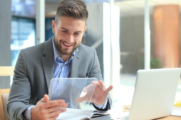 Zakenman werken op kantoor met transparante tablet en laptop.