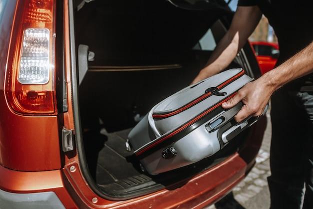 Zakenman, werknemer die zich klaarmaakt voor zakenreis naar het buitenland, legt bagage in de kofferbak van een auto