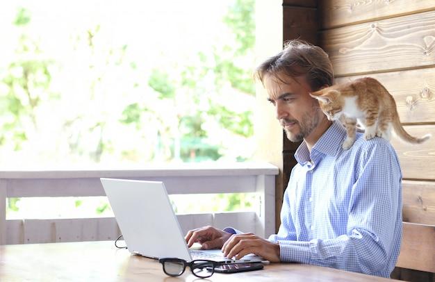 Zakenman werkt aan laptop op een open terras, kitten zit op zijn schouder