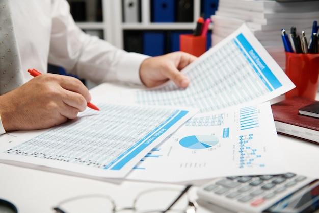 Zakenman werkt en berekent, leest en schrijft rapporten. beambte, tafel close-up. bedrijfsconcept financiële boekhouding.