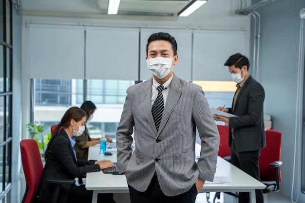Zakenman werkt en draagt een masker ter bescherming van covid-19 of coronavirusziekte op het modelkantoor.
