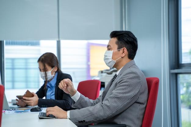 Zakenman werkt en draagt masker ter bescherming van covid-19 of coronavirusziekte op modern kantoor.
