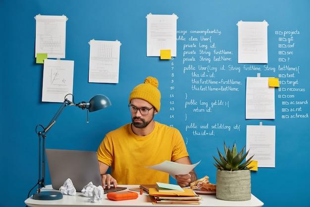 Zakenman werkt met papieren, betrokken bij werkproces op kantoor, denkt na over plan