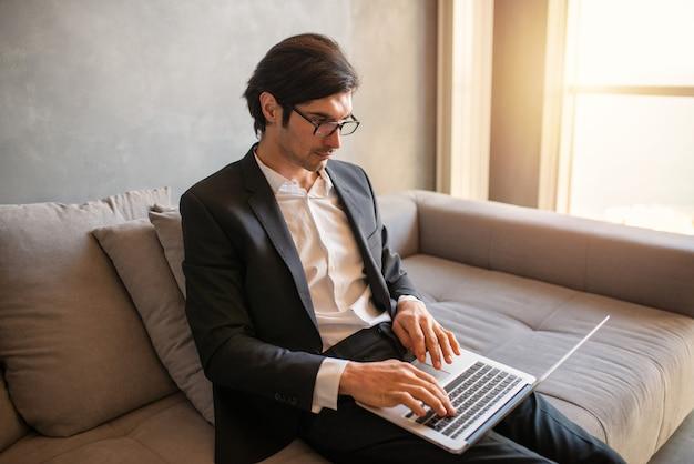 Zakenman werkt op afstand thuis met een laptop vanwege de quarantaine van het coronavirus.