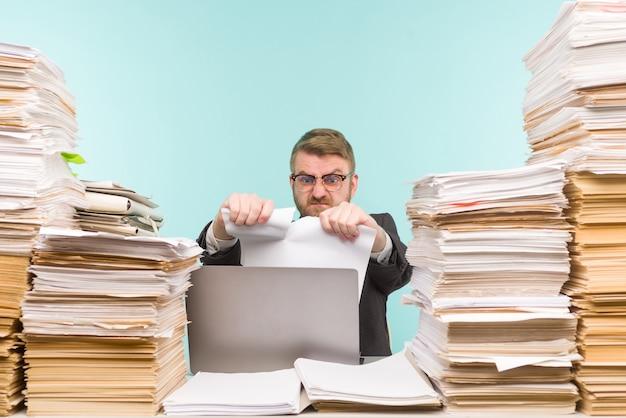 Zakenman werkzaam op kantoor en stapels papierwerk