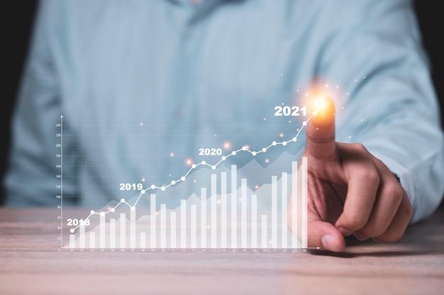 Zakenman wijst naar virtuele investeringsbalk en lijngrafiek op houten tafel als bedrijfsstrategie en aandelenwaarde investeerder concept.