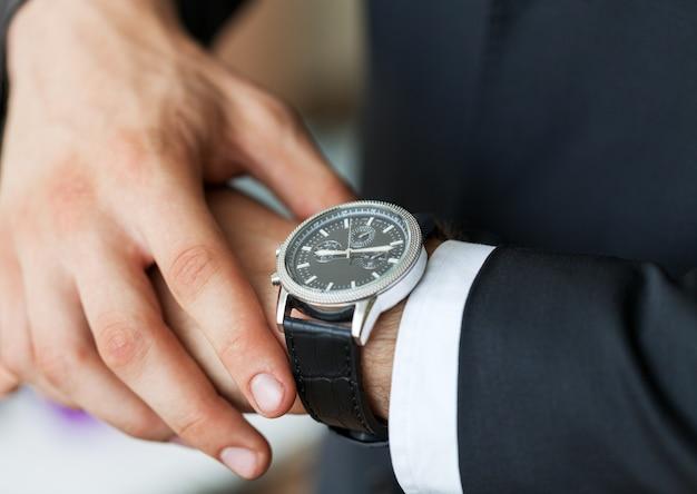Zakenman wijzend bij de hand horloge op grijze muur achtergrond, close-up
