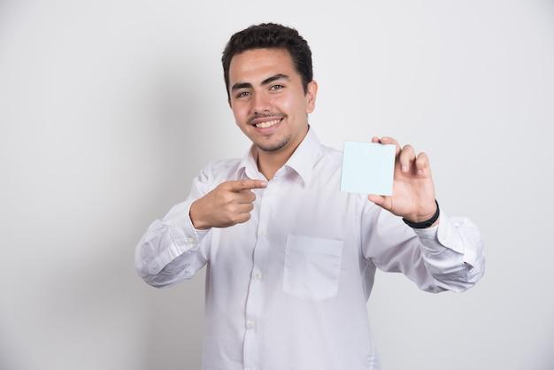 Zakenman wijzend op memoblokken op witte achtergrond.